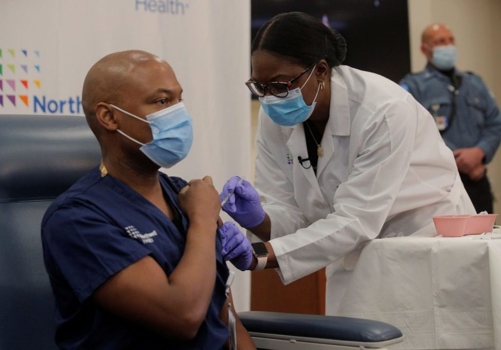 Dr Yves Duroseau from Lennox Hill Hospital is inoculated with the coronavirus disease (COVID-19) vaccine by Dr. Michelle Chester from Northwell Health at Long Island Jewish Medical Center in New Hyde Park, New York, U.S., December 14, 2020. REUTERS/Brendan Mcdermid